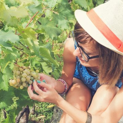 Cute young woman tasting organic grapes outdoors.